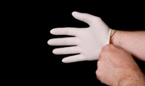 Homme enfilant un gant en latex