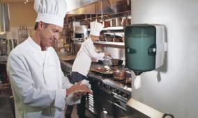 Cuisnier s'essuyant les mains devant un distributeur de papier