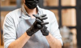 Personne portant un masque et des gants noir